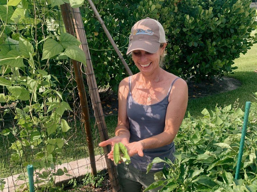 Farm Stand's gardener, Heidi Hoover, standing in the garden holding winged beans.