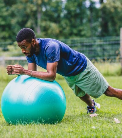 Fitness trainer Ifa Simmonds performing a plank on an exercise ball.