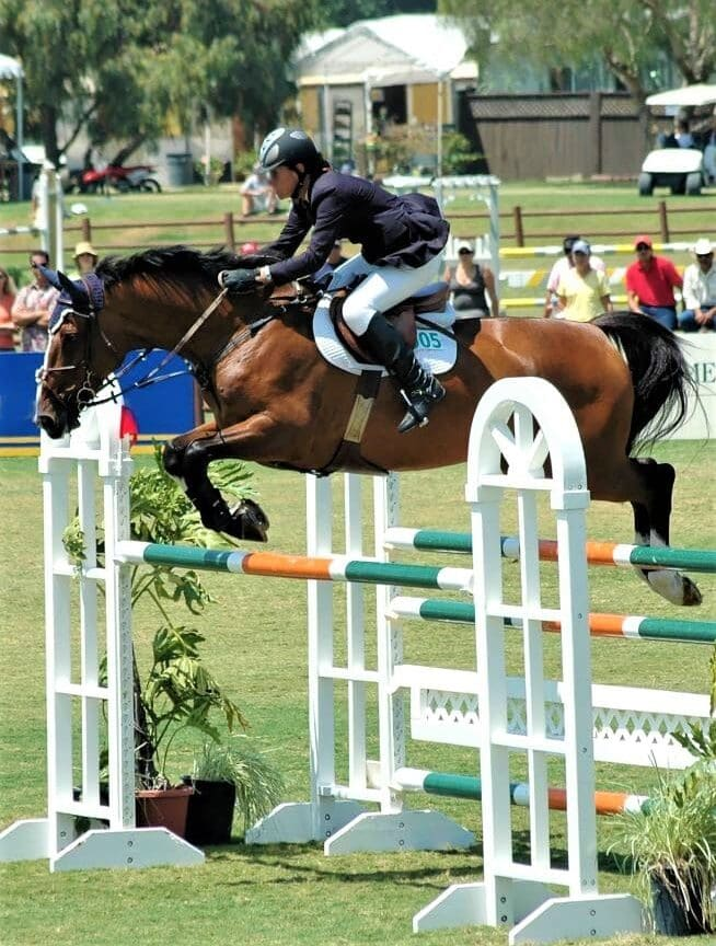 A man jumping a performance horse at a show.