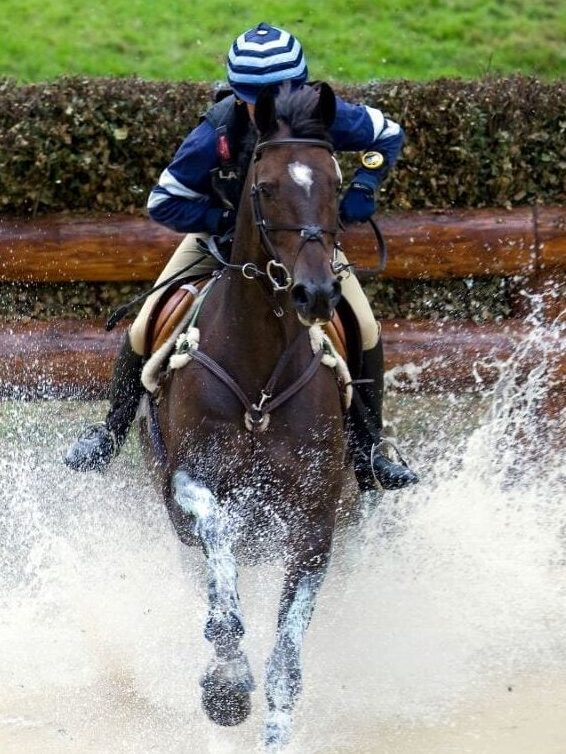 Someone riding an eventing performance horse through a water jump.