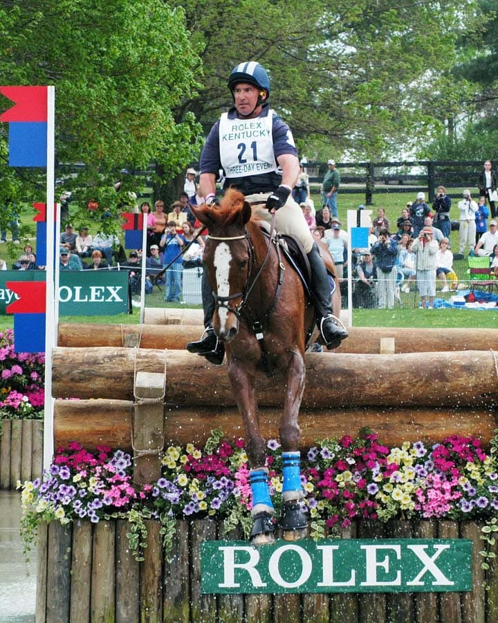 David O'Connor riding over a log jump into water on a cross country course while competing at the Rolex Kentucky Three-Day Event.